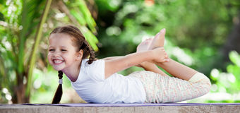 Barn som utomhus gör övning på plattformen Sund livsstil isolerad vit yoga för bakgrund flicka arkivbild