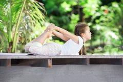 Barn som utomhus gör övning på plattformen Sund livsstil isolerad vit yoga för bakgrund flicka arkivfoto