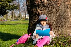 Barn som utomhus läser boken i parkera royaltyfri bild