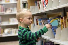 Barn som väljer en bok från arkivhyllan royaltyfri fotografi