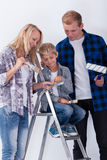 Barn som väljer en färg för att måla ett rum Arkivfoto