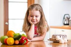 Barn som väljer mellan sunda grönsaker och Arkivbilder