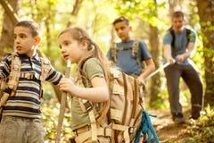 Barn spanar, och fadern undersöker den härliga skogen Arkivbild
