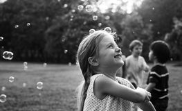 Barn spelar bubblor i en parkera arkivfoton