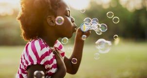 Barn spelar bubblor i en parkera royaltyfri foto