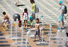 Barn spelar en springbrunn Arkivfoto