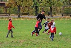 Barn spelar fotboll i stad parkerar arkivbild