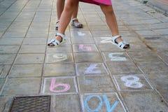 Barn spelar hoppa hage Arkivfoto