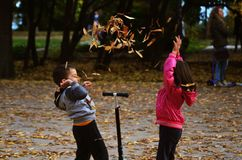 Barn spelar i höstdagar Arkivbild