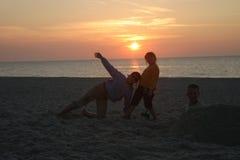 barn spelar s-solnedgång Royaltyfri Foto