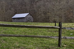Barn and split rail fence during a snow flurry Royalty Free Stock Images