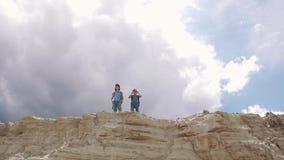 Barn står på kanten av en klippa i bergen och tycker om den härliga sikten stock video