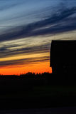 Barn Sunset Vertical. Vertical silhouette of a barn in front of a colorful sunset Royalty Free Stock Photos