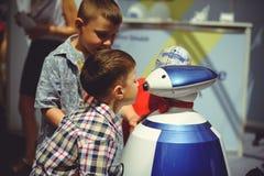 Barn talar till en robot på gatan royaltyfri bild