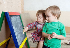 Barn tecknar på blackboarden med krita Arkivbilder