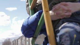 Barn två, gammal syster och liten broder som har gyckel på en gunga på vårdag Skämtsamt utomhus- omgivande, lycka och glädje lager videofilmer