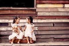 Barn två gulliga asiatiska små flickor sitter på resväskan Arkivfoton