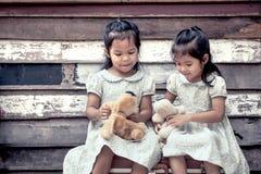 Barn två gulliga asiatiska små flickor sitter på resväskan Arkivbilder