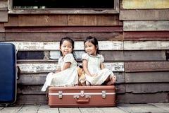 Barn två gulliga asiatiska små flickor sitter på resväskan Arkivfoto