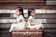 Barn två gulliga asiatiska små flickor sitter på resväskan Royaltyfri Fotografi