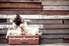 Barn två gulliga asiatiska små flickor sitter på resväskan Arkivbild