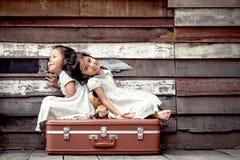 Barn två gulliga asiatiska små flickor sitter på resväskan Fotografering för Bildbyråer