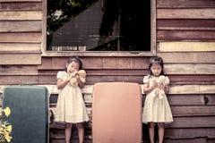 Barn två gulliga asiatiska små flickor som spelar med dockan Royaltyfri Foto