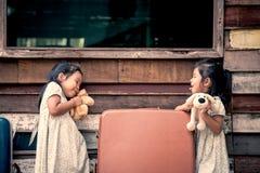 Barn två gulliga asiatiska små flickor som spelar med dockan Arkivfoto