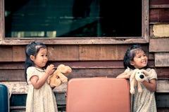 Barn två gulliga asiatiska små flickor som spelar med dockan Arkivfoton