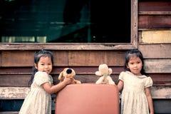 Barn två gulliga asiatiska små flickor som spelar med dockan Fotografering för Bildbyråer