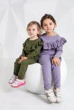 Barn två systrar 1 5 och 5 gamla år i de identiska dräkterna av olika färger, små flickor på en vit Royaltyfria Foton