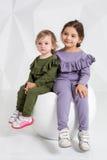 Barn två systrar 1 5 och 5 gamla år i de identiska dräkterna av olika färger, små flickor på en vit Arkivbild