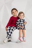 Barn två systrar 1 5 och 5 gamla år i dräkterna av olika färger, små flickor på en vit bakgrund i Royaltyfria Bilder