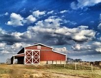 Barn Under Clouds. Modern red barn out in the country under a bold blue sky with fluffy clouds between Royalty Free Stock Images