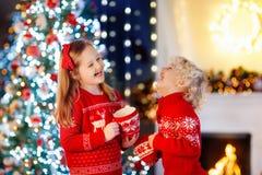 Barn under julgranen hemma Pys och flicka i stucken tröja med varm choklad för Xmas-prydnaddrink Familj med arkivfoto
