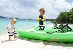 Barn ungar som har gyckel på den tropiska stranden nära havet Royaltyfria Bilder