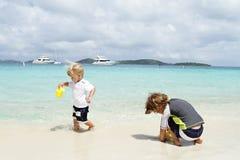 Barn ungar som har gyckel på den tropiska stranden nära havet Royaltyfri Bild