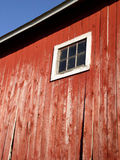 Barn Window. The side of a red, wooden barn with a small white window.  The barn boards are starting to give out and the paint is well faded Royalty Free Stock Images