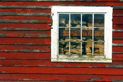 Barn Window. Window on a old red barn with firewood showing on the inside Stock Photography