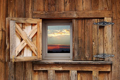 Barn Window. Open barn window framing a surreal sunset Stock Image