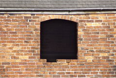Barn window with no glass and a brick missing. Barn window with a brick missing in the surround Stock Image