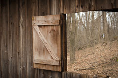 Barn window opened to a early spring woods. An open barn door window opens to a leaf strewn woods in the early spring in Michigan USA royalty free stock photo