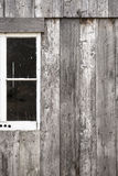 Barn window. Picture of the outside wall of an old wooden barn with a white framed window. The composition of the picture cuts the window in half and leaves a Stock Photography
