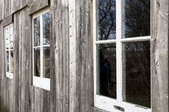 Barn windows 2. Picture of the outside wall of a wooden barn with three white framed windows shown in perspective Royalty Free Stock Photo