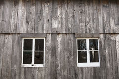 Barn windows. Picture of the outside wall of a wooden barn, with 2 white framed windows Royalty Free Stock Photos
