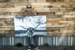 Barn wood background with a man holding art. stock photography
