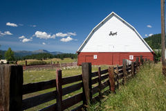 Barn and wood fence. Red and white barn with a wood post fence Stock Photography