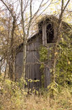 BArn in the woods. An old, neglected barn in the woods of an abandoned farm surrounded by trees in fall foliage Royalty Free Stock Photo