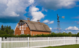 Barn Yard. A old red barn along with a weather vane shot behind a white picket fence Stock Image