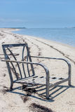 Barnacle Chair. Deserted chair sitting on exposed sandbar Stock Photo